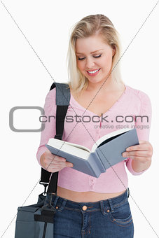Smiling blonde woman reading a novel