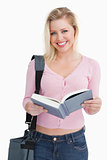 Happy blonde woman holding a novel and her shoulder bag