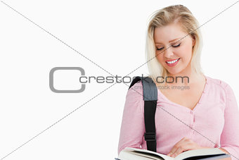 Smiling blonde woman reading an interesting novel