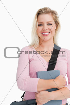 Blonde woman staring at the camera while holding a book