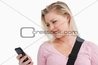 Blonde woman standing while sending a text