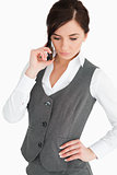 Attractive woman in suit looking down while phoning