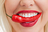 Happy blonde woman holding a chili with her mouth