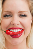 Cheerful blonde woman placing a chili between her teeth
