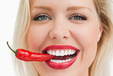 Happy blonde woman biting a red chili pepper