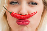 Cheerful woman placing a chili between her nose and her mouth