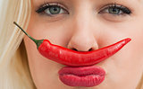Young woman placing a chili between her nose and her mouth