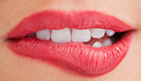 White teeth of a woman biting her lips