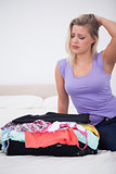 Young woman rubbing her head while looking at her full suitcase