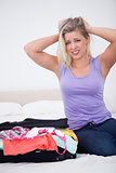 Blonde tearing her hair with her full suitcase