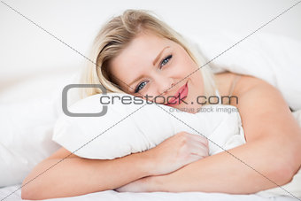 Blonde smiling while embracing a pillow