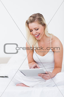 Blonde laughing while using an ebook