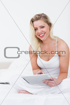 Blonde smiling while holding an ebook