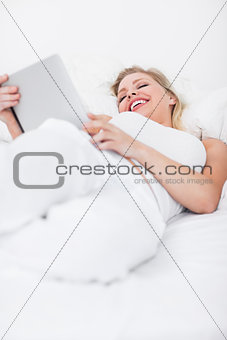 Blonde laughing while using an ebook reader