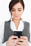 Brunette in suit reading a text-message