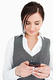 Smiling young businesswoman text-messaging 