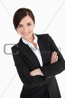 Smiling blue eyed woman in suit with arms folded