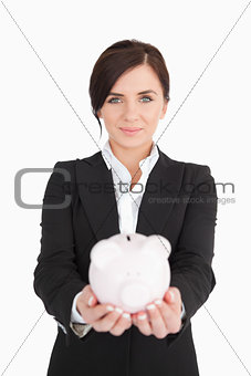 Beautiful businesswoman holding a piggy-bank