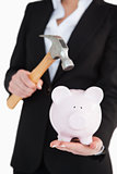 Businesswoman holding a piggy-bank and a hammer
