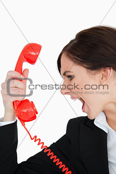 Woman in suit screaming on a red dial telephone