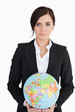 Beautiful woman in suit holding an earth globe