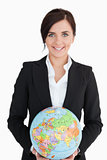 Smiling woman in suit holding an earth globe
