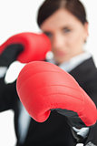 Businesswoman boxing with red gloves