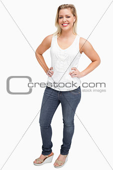 Smiling blonde woman placing her hands on her hips