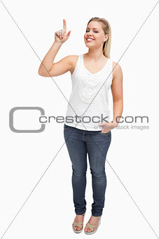 Smiling blonde woman pointing her finger up