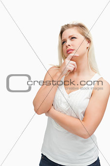 Blonde woman placing her fingers on her chin while crossing her
