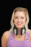 Cheerful blonde woman standing with headphones around her neck