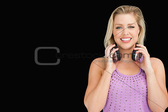 Smiling attractive woman holding her headphones