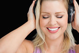 Smiling blonde woman wearing her headphones