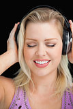 Joyful blonde woman wearing her headphones