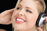 Happy blonde woman listening to music through headphones