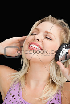 Joyful blonde woman listening to music with headphones