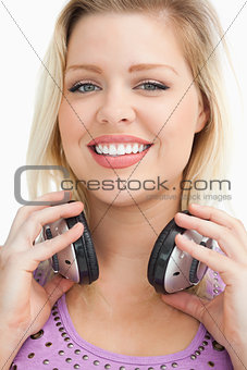 Smiling blonde woman standing while holding headphones