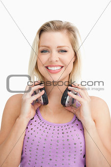 Fair-haired woman holding her headphones