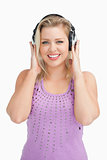 Happy blonde woman placing her hands on her headphones
