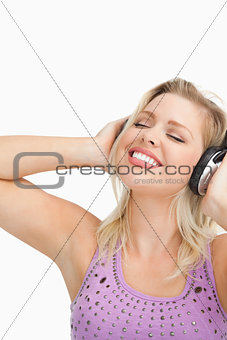 Blonde woman leaning her head while listening to music
