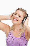 Smiling blonde woman wearing headphones while touching them