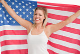 Joyful blonde woman holding the Stars and Stripes flag