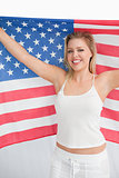 Happy blonde woman holding the Old Glory flag