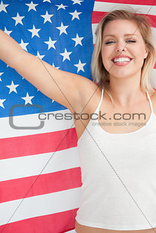 Cheerful blonde woman raising the Stars and Stripes flag