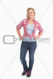 Happy blonde woman standing with her hands on her hips
