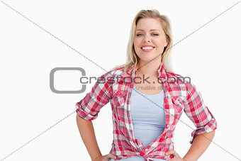 Smiling blonde woman putting her hands on her hips