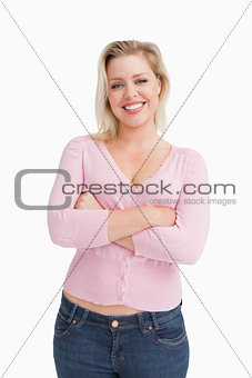 Smiling blonde crossing her arms while standing