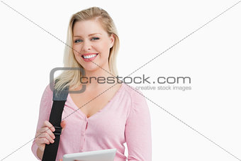 Smiling blonde woman holding a shoulder bag with a tablet pc
