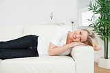 Casual woman lying on a white sofa