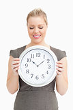 Woman looking at a clock in her hands